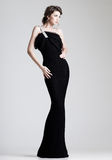 Den härliga kvinnan modellerar att posera i elegant klänning i studion Royaltyfria Bilder