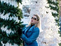 Den härliga kvinnan omfamnar en kolonn med jullandskap Arkivfoto