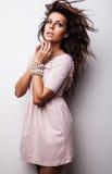 Den härliga kvinnan på den trendiga klänningen poserar i studio. royaltyfri bild