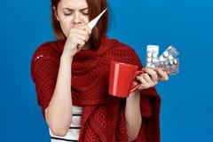 Den härliga kvinnan på en blå bakgrund rymmer en råna, preventivpillerar, termometern, sjukdomen som är sjuk, influensa royaltyfria bilder