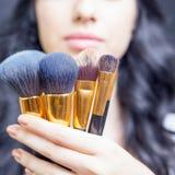 Den härliga kvinnan på skönhetsalongen med uppsättningen av makeup borstar Arkivbild