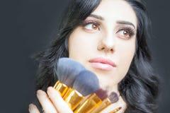 Den härliga kvinnan på skönhetsalongen med uppsättningen av makeup borstar Royaltyfri Foto