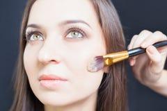 Den härliga kvinnan på skönhetsalongen mottar makeup Arkivfoto