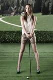 Den härliga kvinnan plays golf med golfen-club Arkivfoto