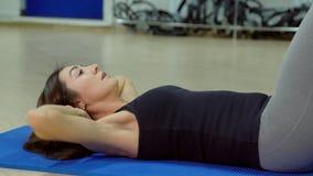 Den härliga kvinnan pumpar buk- muskler i konditionmitt arkivfoto