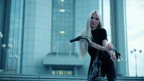 Den härliga kvinnan rider en cykel nära en högväxt buildin Arkivbilder