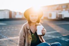 Den härliga kvinnan rymmer kaffekoppen på solnedgång Royaltyfria Bilder