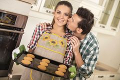 Den härliga kvinnan rymmer den varma stekheta pannan med kakor Den lyckliga maken är kyssande henne royaltyfria bilder