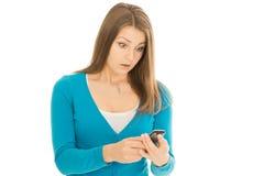 Den härliga kvinnan ser den förvånade telefonen Arkivbild