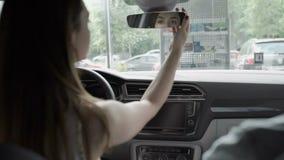 Den härliga kvinnan ser i backspegel i kabin för bil` s stock video