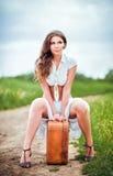 Den härliga kvinnan sitter på en resväska nära den lantliga vägen Arkivfoton