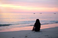 Den härliga kvinnan sitter på stranden arkivfoto