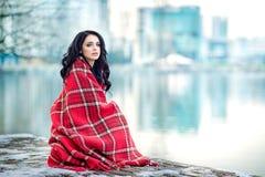 Den härliga kvinnan sitter utomhus på pir med den röda plädet Arkivfoton