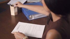 Den härliga kvinnan skriver och undertecknar rättegång på kontoret av advokaten