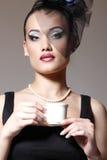 Den härliga kvinnan skyler in den retro glamourskönhetståenden Royaltyfri Fotografi