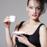 Den härliga kvinnan skyler in den retro skönhetståenden med kopp te eller Royaltyfria Foton