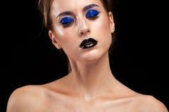 Den härliga kvinnan som bär överdådiga blått, utgör med svarta kanter Arkivbilder