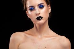 Den härliga kvinnan som bär överdådiga blått, utgör med svarta kanter Arkivfoto