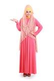 Den härliga kvinnan som bär rosa muslim, klär visningcopyspace arkivfoto