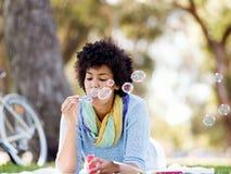 Den härliga kvinnan som blåser bubblor parkerar in Royaltyfri Bild