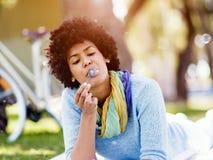 Den härliga kvinnan som blåser bubblor parkerar in Royaltyfria Bilder