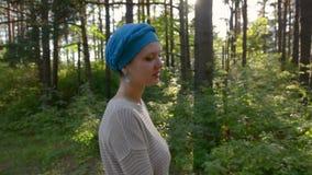 Den härliga kvinnan som går i skogen i den blåa turbanen, sol blossar bakom Semestrar begrepp lager videofilmer