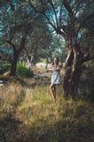 Den härliga kvinnan som går i sommar, parkerar med olivträd på solnedgång Kvinnligt långt hår för brunbränd brunett i den vita kl Arkivfoton