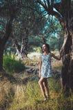 Den härliga kvinnan som går i sommar, parkerar med olivträd på solnedgång Kvinnligt långt hår för brunbränd brunett i den vita kl Royaltyfri Fotografi