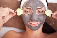 Den härliga kvinnan som har den ansikts- maskeringen för lera, applicerar vid beauticianen Royaltyfri Foto