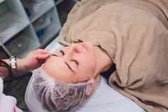 Den h?rliga kvinnan som har en ansikts- sk?nhetsmedel, skurar behandling fr?n yrkesm?ssig hudspecialist p? wellnessbrunnsorten An royaltyfria foton