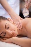 Den härliga kvinnan som har en wellness tillbaka, masserar. nätt kvinna som lägger på massagetabellen och får olje- massage fotografering för bildbyråer