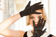 Den härliga kvinnan som inramar henne blått, synar med svart handskar Royaltyfri Bild