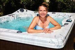 Den härliga kvinnan som kopplar av i varmt, badar royaltyfri foto