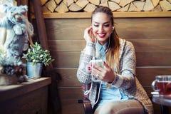 Den härliga kvinnan som lyssnar till musik med headphonen, medan dricka kaffe med mening lycklig, och kopplar av i kafé royaltyfria foton