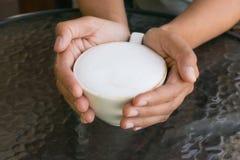 Den härliga kvinnan som rymmer den varma koppen kaffe med mer, mjölkar skum på den glass tabellen Arkivfoto