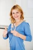 Den härliga kvinnan som rymmer ett exponeringsglas av vatten och visar, tummar upp s Arkivbilder