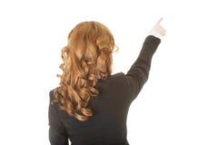 Den härliga kvinnan som står och pekar upp, beskådar tillbaka. royaltyfri foto