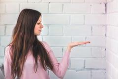 Den härliga kvinnan står en vit tegelstenbakgrund och håller på något på hennes hand och att se på den royaltyfria foton