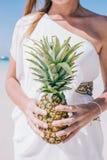 Den härliga kvinnan står på en vit sandig strand vid havet En flicka i en vit klänning rymmer en gul ananas i henne händer arkivfoto