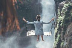 Den härliga kvinnan svänger nära vattenfallet i djungeln av den Bali ön, Indonesien royaltyfri bild