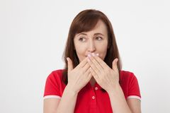 Den härliga kvinnan täcker hennes mun med hennes isolerade händer för tyst Röd tshirt och hålla en hemlighet royaltyfri fotografi
