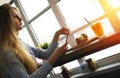 Den härliga kvinnan tänker om något och att sitta med en telefon i hans hand i det moderna kafét Royaltyfria Foton