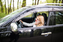 Den härliga kvinnan talar på mobiltelefonen och ler, medan sitta i bilen royaltyfri bild