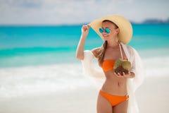 Den härliga kvinnan tar bort törstat med kokosnöten mjölkar Royaltyfri Bild