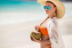 Den härliga kvinnan tar bort törstat med kokosnöten mjölkar Arkivbilder