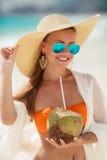 Den härliga kvinnan tar bort törstat med kokosnöten mjölkar Arkivfoton