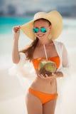 Den härliga kvinnan tar bort törstat med kokosnöten mjölkar Royaltyfri Fotografi