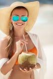 Den härliga kvinnan tar bort törstat med kokosnöten mjölkar Arkivfoto