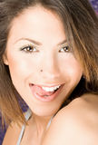 Den härliga kvinnan trycker på henne upp kanten vid tungan Arkivfoto