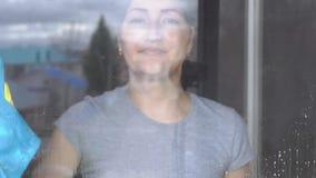 Den härliga kvinnan tvättar fönstret med en blått trasa och rengöringsmedel stock video